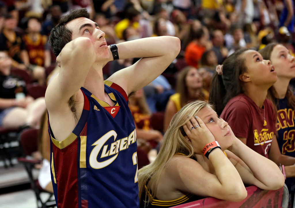 . Alex D\'Alessio, left, and Kylie Siegel watch during the final minute of Game 5 of basketball\'s NBA Finals between the Golden State Warriors and the Cleveland Cavaliers at watch party at Quicken Loans Arena, Monday, June 12, 2017, in Cleveland. (AP Photo/Tony Dejak)