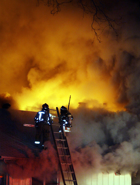 Chico Fire Capt. Steve Harrison (left) and Firefighter Jeff Trost stare right into the flames and smoke as they arrive atop the roof to respond to a house fire at 51 Terrace Dr. Tuesday around 8:00pm. Crews from all over Chico came out to extinguish the fire that had completely engulfed the two story home.  The fire was concentrated in the rear of the home. No one was reported to be in the home at the time of the fire. - halley photo 1/31/06