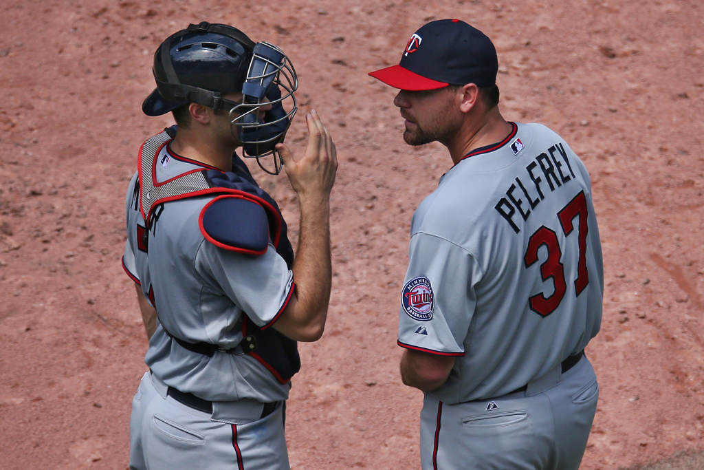 . Twins pitcher Mike Pelfrey  talks to  catcher Joe Mauer. (Photo by Tom Szczerbowski/Getty Images)