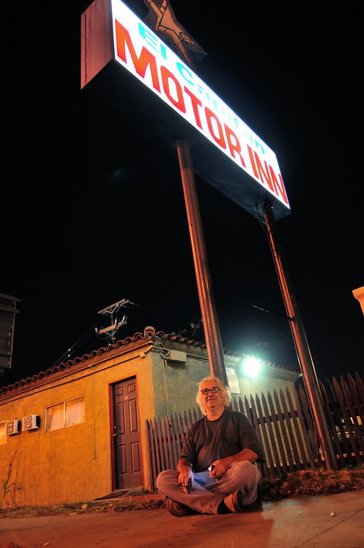 . Tim Grobaty rests under the sign advertising the El Capitan Motor Inn.Photo by Thomas Wasper for the Press Telegram