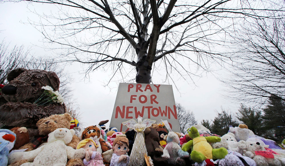 Description of . Stuffed animals and a sign calling for prayer rest at the base of a tree near the Newtown VIllage Cemetery in Newtown, Conn., Monday, Dec. 17, 2012. Six-year-old student Jack Pinto, who was killed Friday when a gunman opened fire inside the Sandy Hook Elementary School, is scheduled to be buried at the cemetery Monday afternoon. (AP Photo/Charles Krupa)