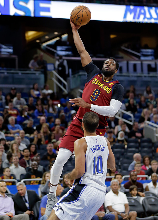 . Cleveland Cavaliers\' Dwyane Wade (9) shoots over Orlando Magic\'s Evan Fournier (10) during the first half of an NBA preseason basketball game, Friday, Oct. 13, 2017, in Orlando, Fla. (AP Photo/John Raoux)