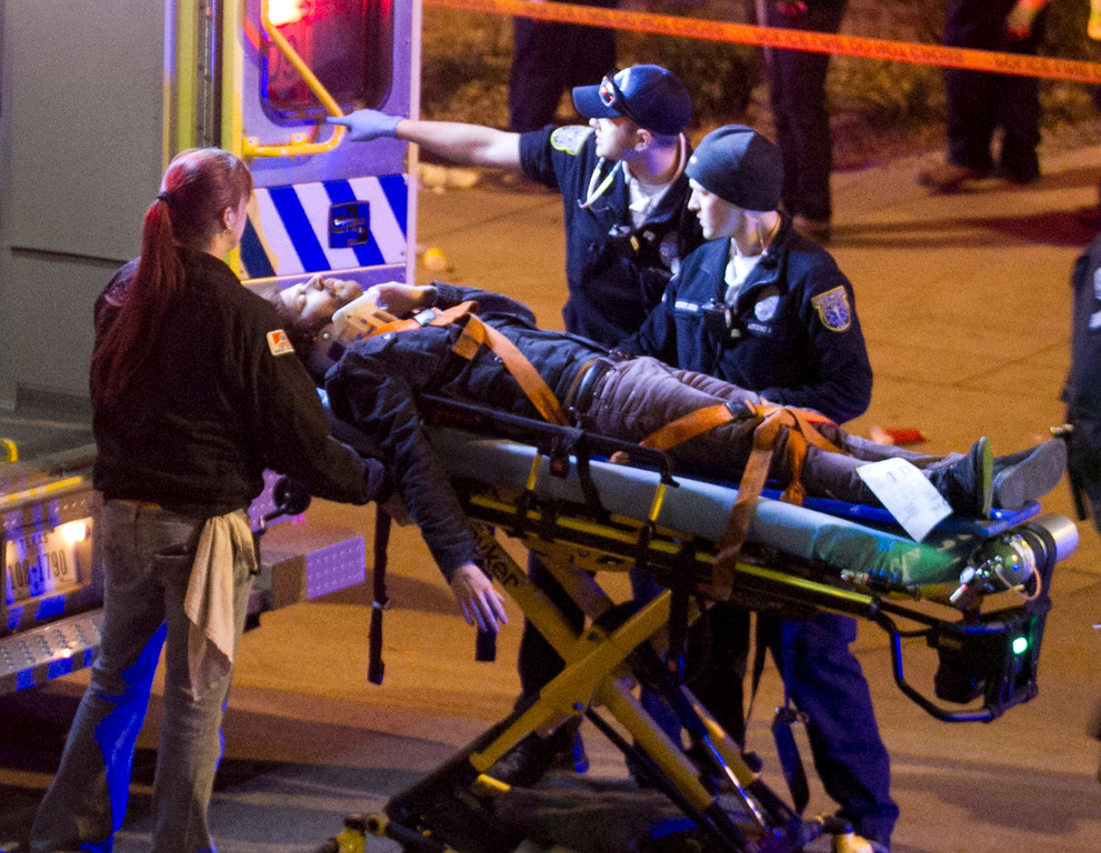 . A man is transported to an ambulance after being struck by a vehicle on Red River Street in downtown Austin, Texas, on Wednesday March 12, 2014.  (AP Photo/Austin American-Statesman, Jay Janner)