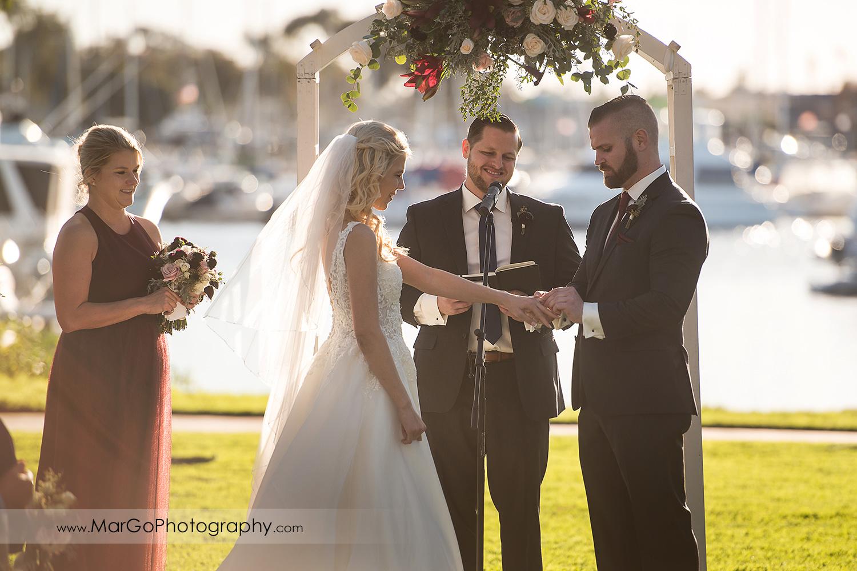 groom putting wedding ring on bride's finger during wedding ceremony at San Diego Marina Village