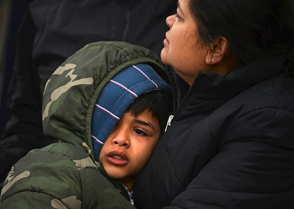 . AURORA, CO - MARCH 24: Blanca Palomino holds her son, seven-year-old Sergio Dominguez as they gather with other friends and family at the corner of East Colfax Avenue and Dayton Street in Aurora where Blanca\'s older son, Juan Carlos Dominguez-Palomino, was killed earlier in a fatal crash, Monday, March 24, 2014.  (Photo by RJ Sangosti/The Denver Post)