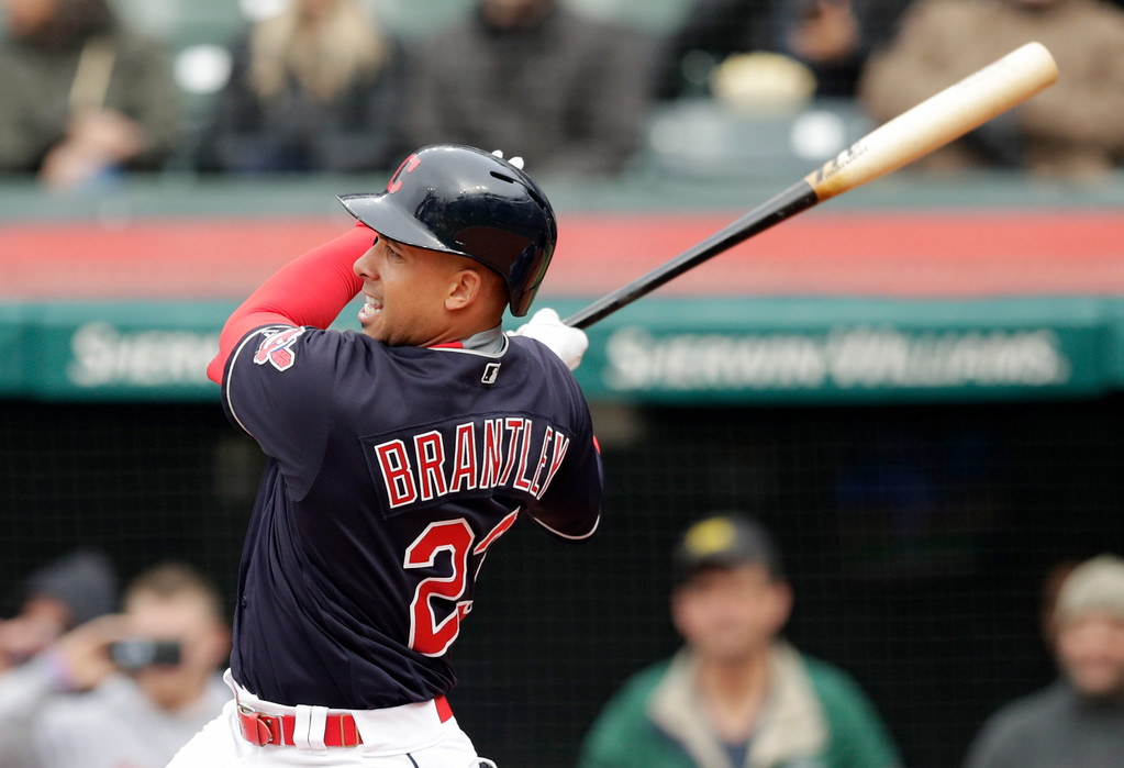 . Cleveland Indians\' Michael Brantley hits an RBI-single off Kansas City Royals starting pitcher Jakob Junis in the first inning of a baseball game, Saturday, May 12, 2018, in Cleveland. Francisco Lindor scored on the play. (AP Photo/Tony Dejak)
