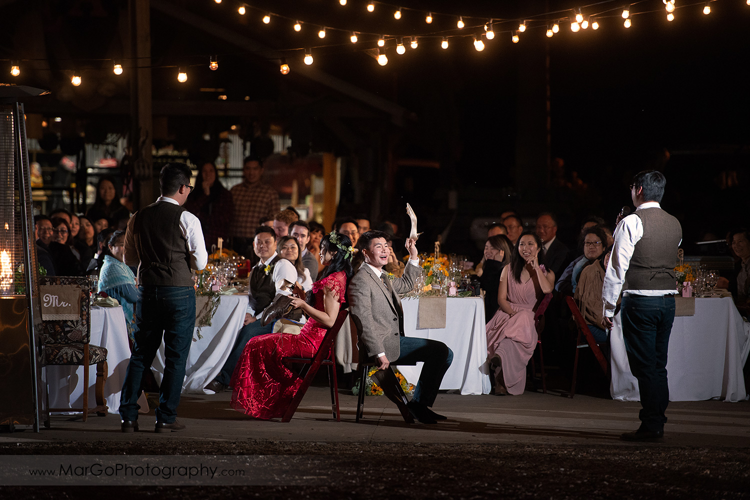 groom and bride in red dress playing shoe game during wedding reception at Long Branch Saloon & Farms in Half Moon Bay