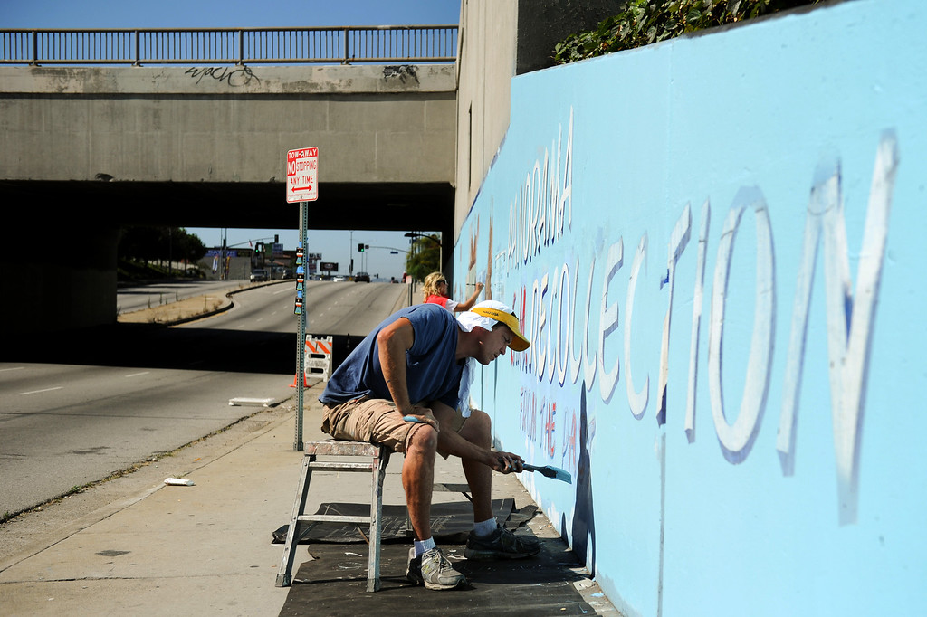 """. Jeff Lingle paints during restoration of the mural \""""Panorama: G.M. Recollections from the Past,\"""" on Van Nuys Boulevard in Panorama City, Thursday, June 20, 2013. The original mural was painted by Alfredo Diaz Flores in 1998 and pays homage to the General Motors plant that used to be near the mural site. (Michael Owen Baker/Staff Photographer)"""