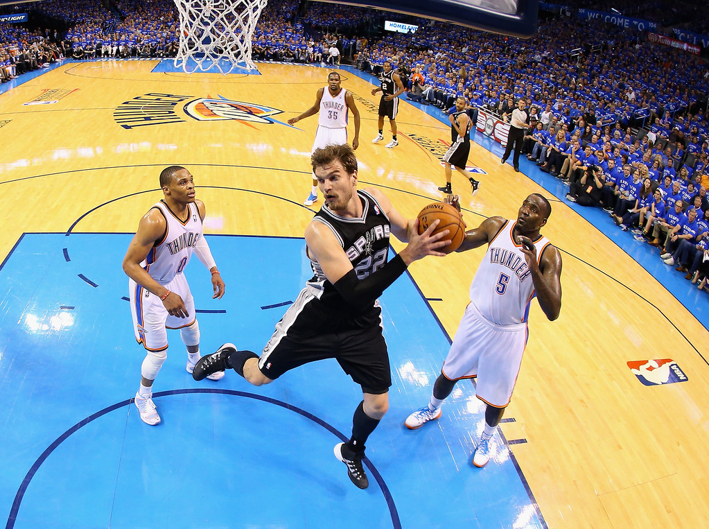 . OKLAHOMA CITY, OK - MAY 25: Tiago Splitter #22 of the San Antonio Spurs gets a rebound against Russell Westbrook #0 and Kendrick Perkins #5 of the Oklahoma City Thunder in the second half during Game Three of the Western Conference Finals of the 2014 NBA Playoffs at Chesapeake Energy Arena on May 25, 2014 in Oklahoma City, Oklahoma.  (Photo by Ronald Martinez/Getty Images)