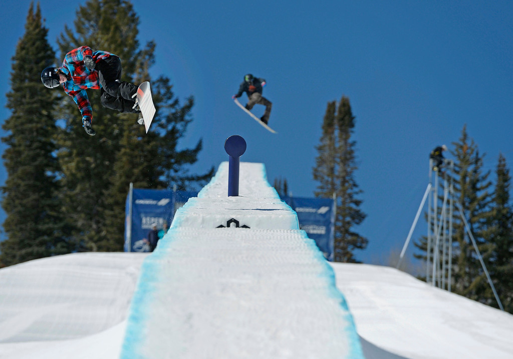 . Professional snowboarder, Benji Farrow, left, and a fellow competitor, right, launch off the 4\' spine of the Red Bull double pipe during practice at Buttermilk Mountain Friday morning, March 21, 2014.  (Photo By Andy Cross / The Denver Post)