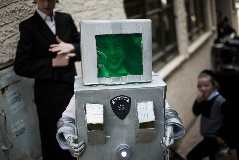 . An ultra-Orthodox Jewish boy wearing a robot costume, stands outside a synagogue, marking the Purim festival in Bnei Brak, near Tel Aviv, Israel, Sunday, March 16, 2014. The Jewish holiday of Purim commemorates the Jews\' salvation from genocide in ancient Persia, as recounted in the Book of Esther which is read in synagogues. Other customs include sending food parcels and giving charity, dressing up in masks and costumes, eating a festive meal and public celebration. (AP Photo/Ariel Schalit)