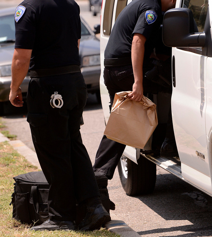 . San Bernardino Police remove a bag of money from a marijuana dispensary along the 3200 block of North E Street in San Bernardino May 9, 2013.  GABRIEL LUIS ACOSTA/STAFF PHOTOGRAPHER.