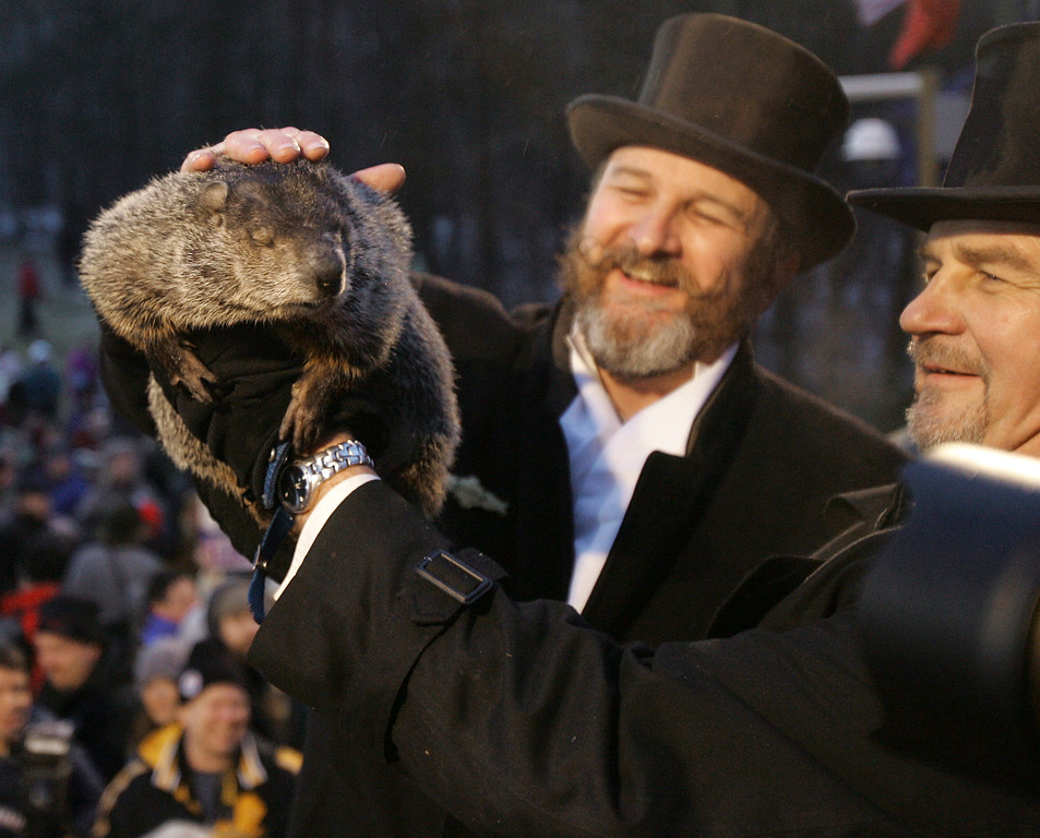 . John Griffiths, right, one of the handlers of weather predicting groundhog Punxsutawney Phil, holds Phil as his other handler, Ben Hughes, pets him on the head Ground Hog\'s Day in Punxsutawney, Pa. on Saturday, Feb. 2, 2008. The Groundhog Club said Phil saw his shadow and predicted six more weeks of winter. (AP Photo/Keith Srakocic)