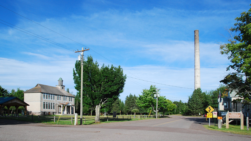 The Sherman Township Hall and Community Center buildings are on the right side of the street leading to the old smokestack. The old township school is on the left.