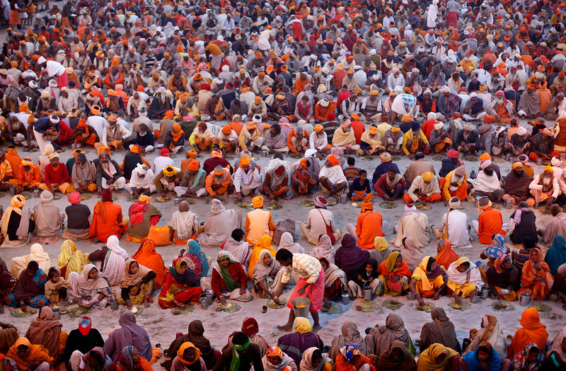 . Hundreds of Hindu holy men are given charitable food on the banks of the river Ganges during the Maha Kumbh festival in Allahabad, India, Tuesday, Jan. 29, 2013. Millions of Hindu pilgrims are expected to attend the Maha Kumbh festival, which is one of the world\'s largest religious gatherings that lasts 55 days and falls every 12 years. During the festival pilgrims bathe in the holy Ganges River in a ritual they believe can wash away their sins. (AP Photo/Rajesh Kumar Singh)