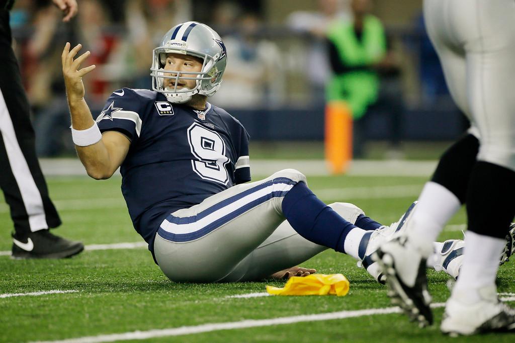 . Dallas Cowboys quarterback Tony Romo (9) reacts against the Oakland Raiders during the first half of an NFL football game, Thursday, Nov. 28, 2013, in Arlington, Texas.  (AP Photo/Tim Sharp)