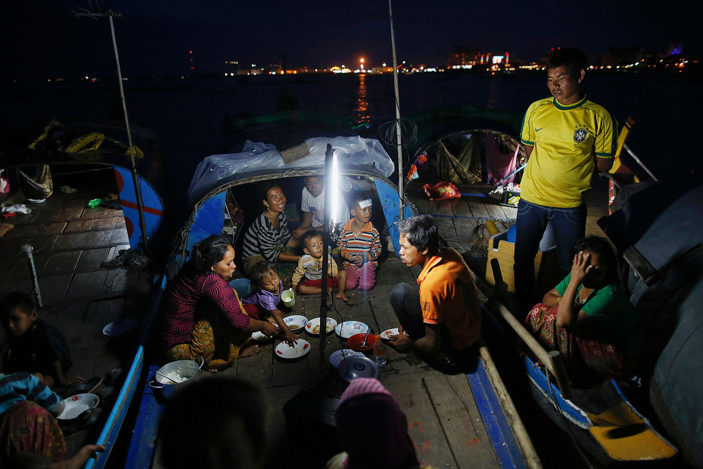 . Ethnic Cham Muslim people eat their iftar (breaking fast) meals on the banks of Tonle Sap river in Phnom Penh July 29, 2013. About 100 ethnic Cham families, made up of nomads and fishermen without houses or land who arrived at the Cambodian capital in search of better lives, live on their small boats on a peninsula where the Mekong and Tonle Sap rivers meet, just opposite the city\'s centre. The community has been forced to move several times from their locations in Phnom Penh as the land becomes more valuable. They fear that their current home, just behind a new luxurious hotel under construction at the Chroy Changva district is only temporary and that they would have to move again soon. Picture taken July 29, 2013.   REUTERS/Damir Sagolj