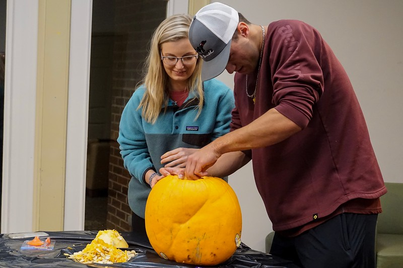 Carey Spratln helps Lacey Warren get started on her pumpkin.