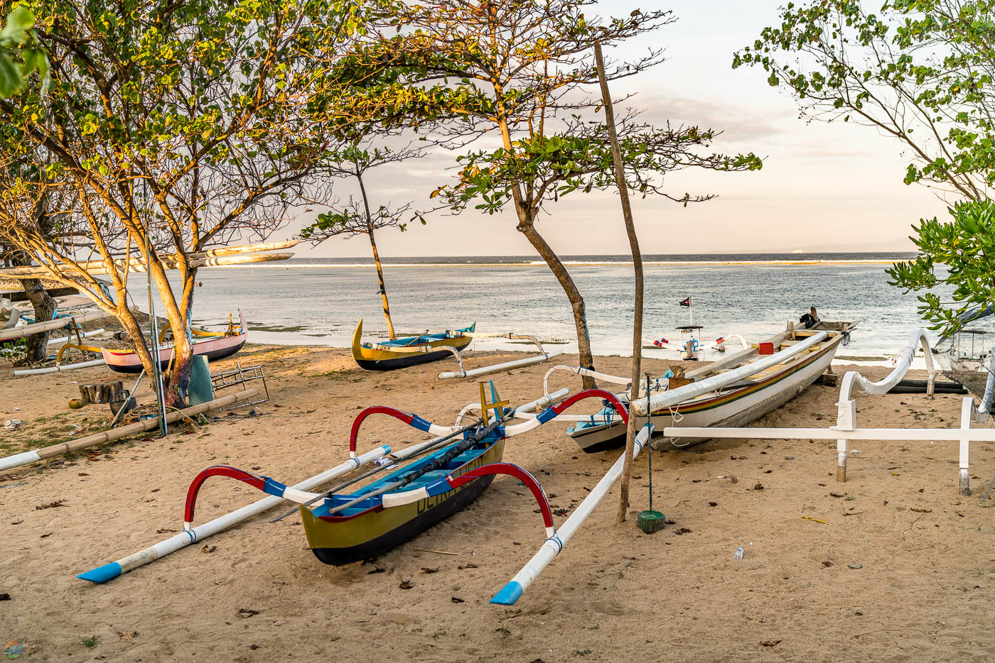 Colorful outrigger boats waiting for passengers on Sanur beach at sunset.