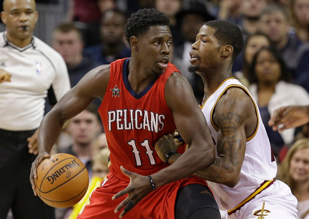 . New Orleans Pelicans\' Jrue Holiday, left, drives against Cleveland Cavaliers\' DeAndre Liggins in the first half of an NBA basketball game, Monday, Jan. 2, 2017, in Cleveland. (AP Photo/Tony Dejak)
