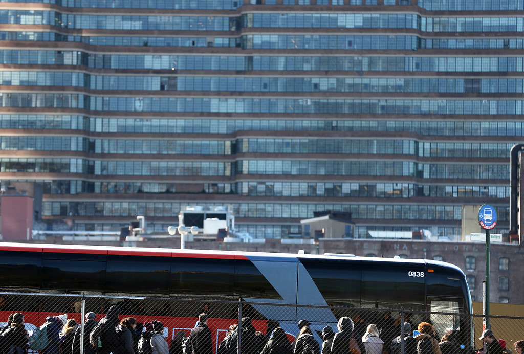 . Travelers board a bus in New York, Wednesday, Nov. 23, 2016. Almost 49 million people are expected to travel 50 miles or more for the Thanksgiving holiday, the most since 2007, according to AAA. (AP Photo/Seth Wenig)