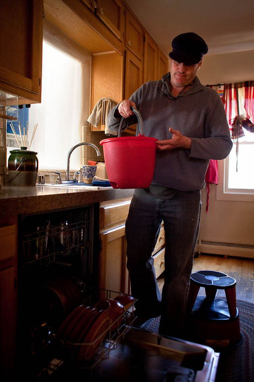 . Nate Downey carries a bucket, used to soak and rinse dishes before they go into a low-water-use dishwasher, to water a tree in his back yard.  (Special to the Pioneer Press: Mark Holm)