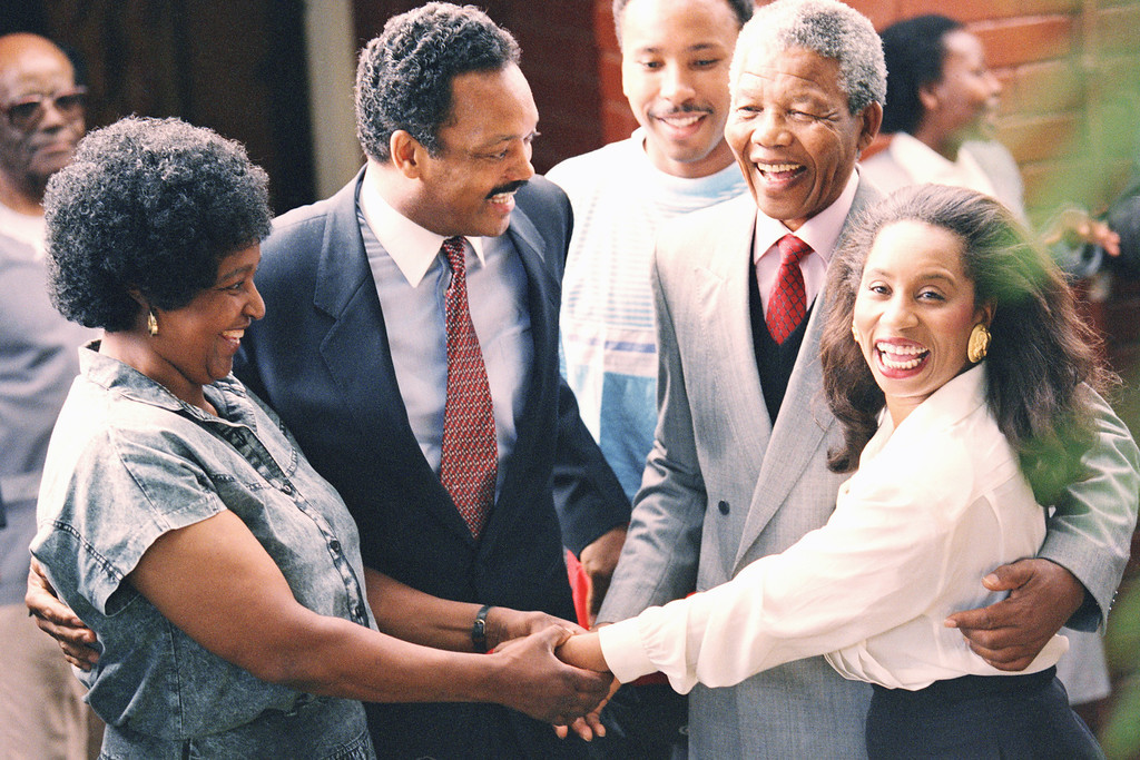 . Former U.S. presidential candidate Jesse Jackson, second from left, and Nelson Mandela, second from right, look on as their wives, Winnie Mandela, left, and Jacqueline Jackson hold hands when the Jacksons visited he Mandelas Soweto home in South Africa, Feb. 15, 1990. Mandela was released from prison last Sunday after serving over 27 years. (AP Photo/Greg English)