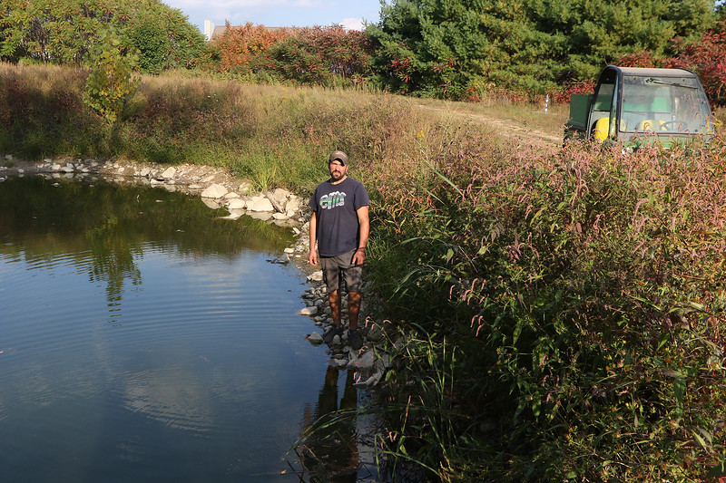 Jim Lattanzi, owner of Hollis Hills Farm in Fitchburg, stands by the pond used for irrigation, where he estimates water level is about 5ft below normal. Normally the water is up to almost the level of the road, and is sufficient for all the farms irrigation needs. Due to the drought, this year they've only gotten about a third of their irrigation water from the pond, needing to buy city water for the rest. (Sentinel & Enterprise/Julia Malakie)