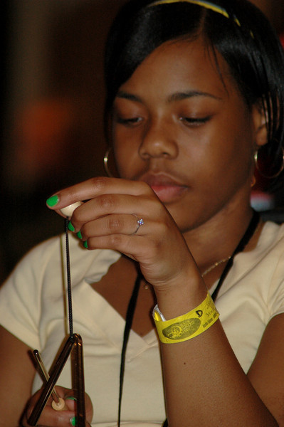 A teenager strikes the triangle as part of a drum circle during Tuesday night worship. (Carrie Draeger, 2009)