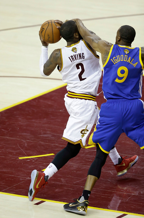. Cleveland Cavaliers guard Kyrie Irving (2) is fouled by Golden State Warriors forward Andre Iguodala (9) in the second half of Game 4 of basketball\'s NBA Finals in Cleveland, Friday, June 9, 2017. (AP Photo/Tony Dejak)