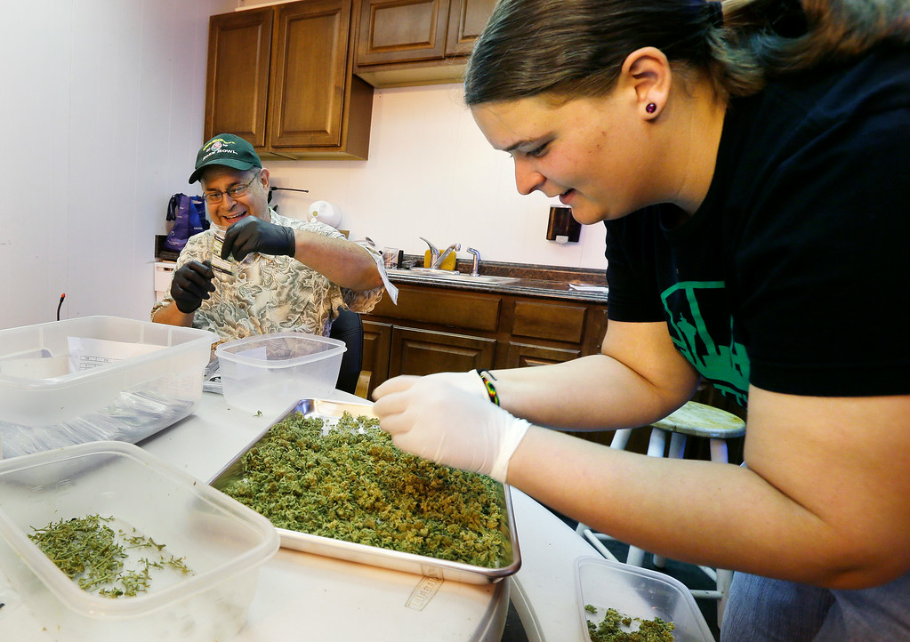 ". In this photo taken July 1, 2014, workers Kristi Tobias, right, and Bruce Cumming prepare packets of a variety of recreational marijuana named ""Space Needle\"" at Sea of Green Farms in Seattle. Workers at the grower, the first business licensed to grow recreational marijuana in Washington state, worked all weekend to have supplies ready for stores that were expected to be granted sale licenses on Monday, the day before the first day of legal recreational pot sales in Washington state. (AP Photo/Ted S. Warren)"