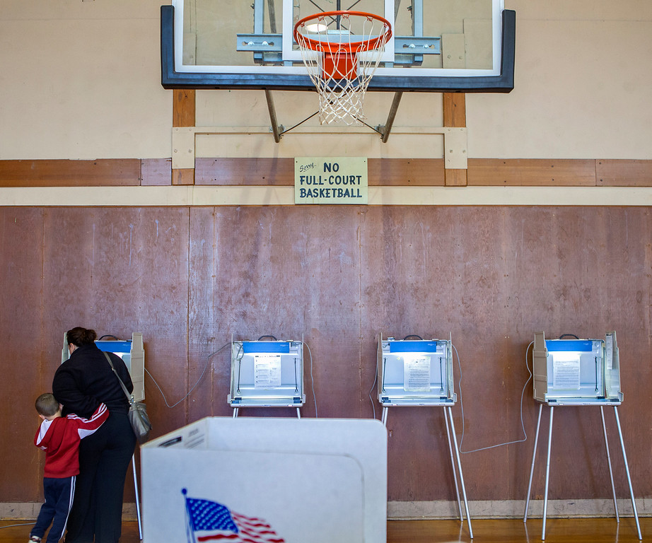 . A voter casts her ballot at the Air Park recreation center basketball gym on Election Day, Tuesday, Nov. 4, 2014 in Lincoln, Neb. (AP Photo/The Journal-Star, Matt Masin)