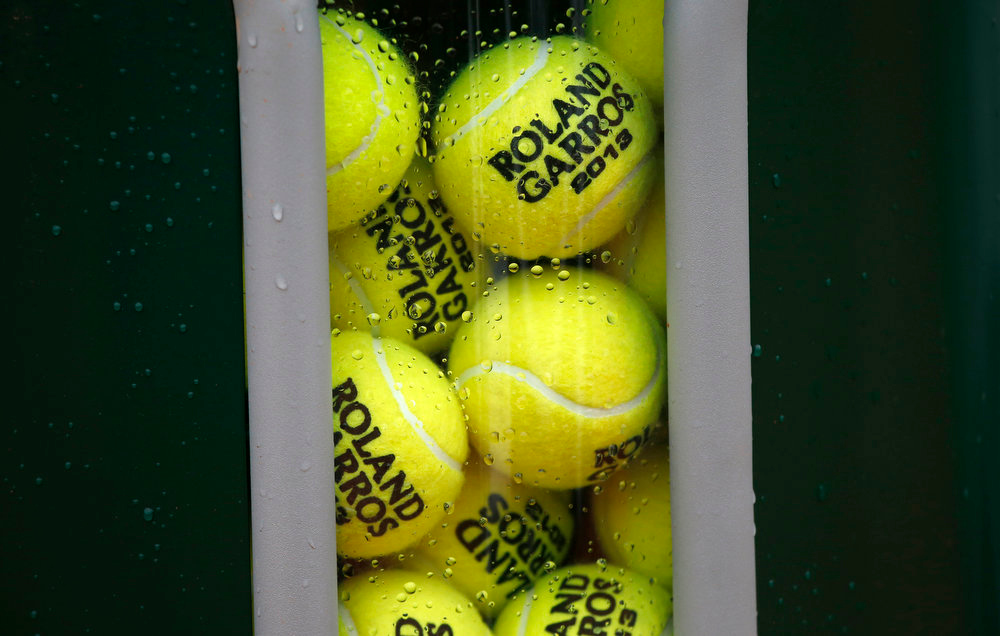 . Official balls are pictured on a court as rain falls on the third day of the French tennis Open at the Roland Garros stadium in Paris on May 28, 2013.  THOMAS COEX/AFP/Getty Images