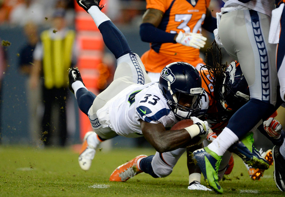 . Running back Christine Michael (33) of the Seattle Seahawks takes the ball to the one yard line and gets hit by strong safety Quinton Carter (38) of the Denver Broncos making it a first and goal during the first half.  The Denver Broncos vs the Seattle Seahawks At Sports Authority Field at Mile High. (Photo by AAron Ontiveroz/The Denver Post)
