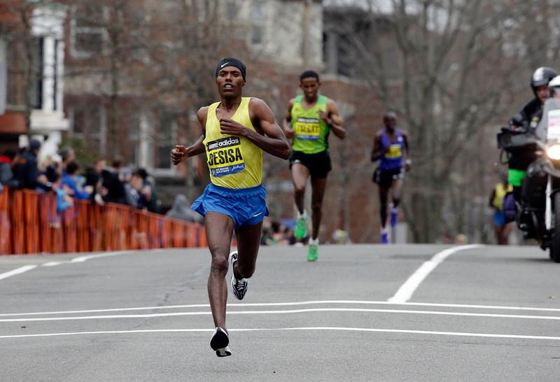 . Lelisa Desisa, of Ethiopia, leads the pack as he runs through Brookline, Mass., en route to a Boston Marathon win, Monday, April 20, 2015, in Boston. (AP Photo/Steven Senne)