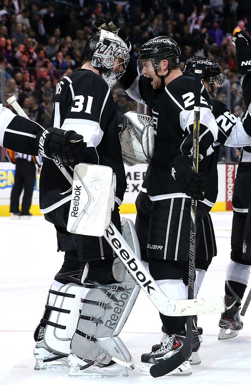 . LOS ANGELES, CA - DECEMBER 21:  Goalie Martin Jones #1 of the Los Angeles Kings is congratulated by Trevor Lewis #22 after Jones stopped all three  Colorado Avalanche shots in the shootout at Staples Center on December 21, 2013 in Los Angeles, California.  The Kings won 3-2 on a shootout.  (Photo by Stephen Dunn/Getty Images)
