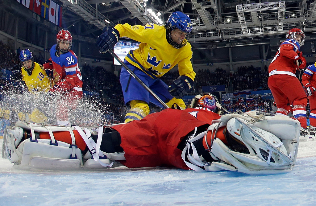 . Sweden\'s Emma Nordin (C) vies with Russia\'s goalkeeper Anna Prugova during the Women\'s Ice Hockey Group B match Sweden vs Russia at the Shayba Arena at the Sochi Winter Olympics on February 13, 2014 in Sochi.   BRIAN SNYDER/AFP/Getty Images