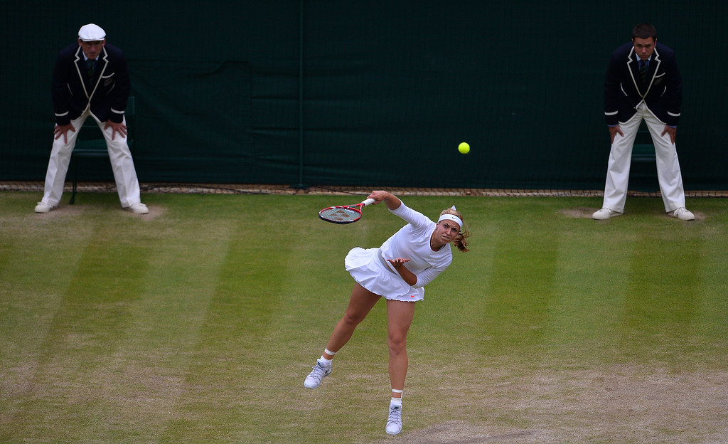 . Germany\'s Sabine Lisicki (C) serves against Estonia\'s Kaia Kanepi during their women\'s quarter final match on day eight of the 2013 Wimbledon Championships tennis tournament at the All England Club in Wimbledon, southwest London, on July 2, 2013. CARL COURT/AFP/Getty Images