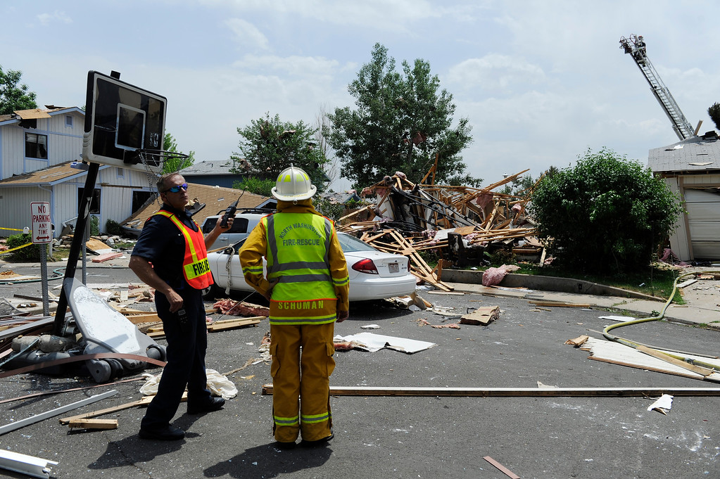 . Fire and fire rescue personal stand by at the scene of the house explosion.  (Photo By Andy Cross/The Denver Post)