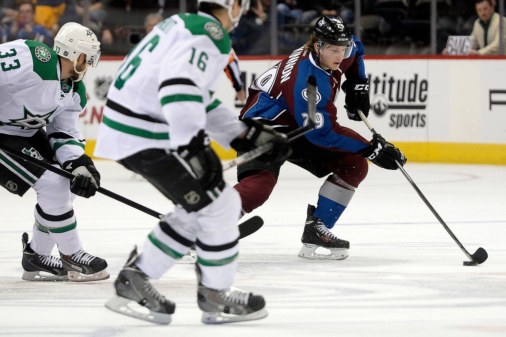 . Colorado Avalanche center Nathan MacKinnon (29) brings the puck up the ice as Dallas Stars left wing Ryan Garbutt (16) and defenseman Alex Goligoski (33) defend during the first period. (Photo by AAron Ontiveroz/The Denver Post)