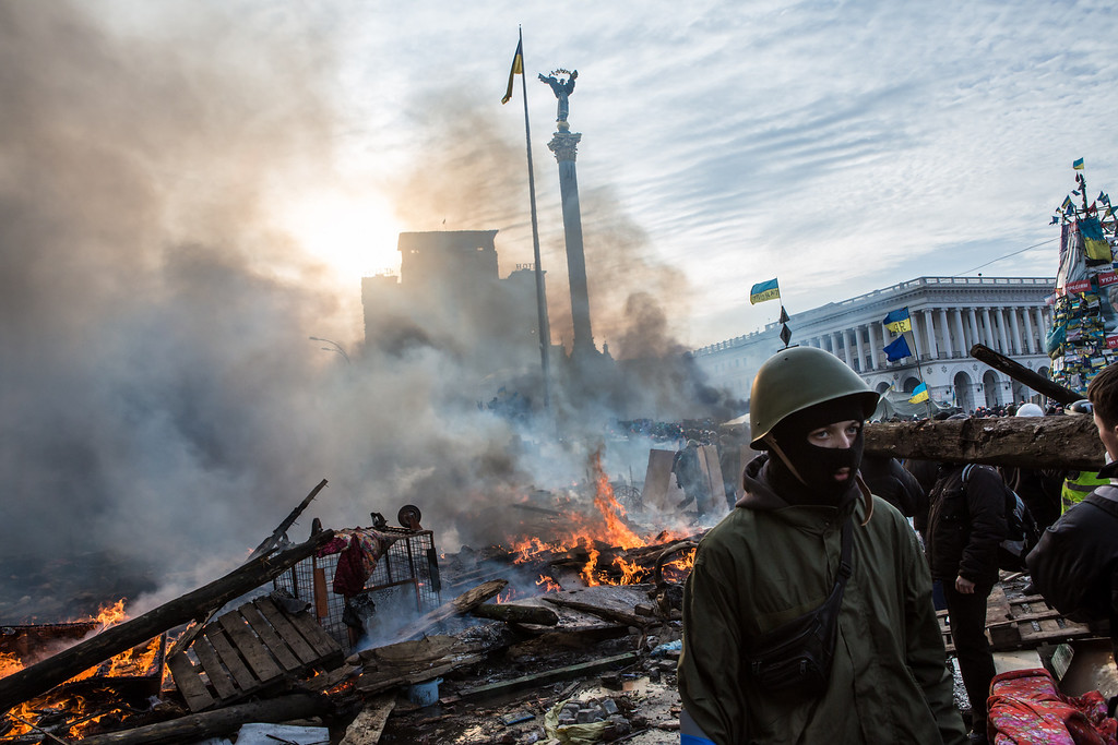 . Anti-government protesters walk amid debris and flames near the perimeter of Independence Square, known as Maidan, on February 19, 2014 in Kiev, Ukraine. (Photo by Brendan Hoffman/Getty Images)