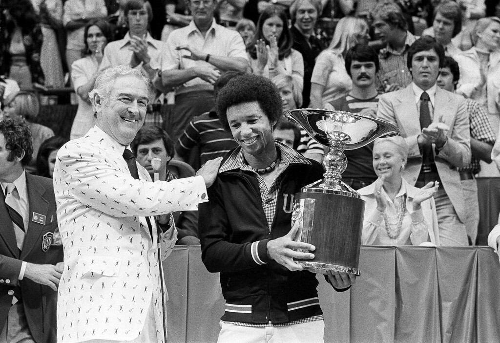 . Former Texas Governor John B. Connally, left, gives Arthur Ashe a pat on the back after the trophy presentation at the World Championship of Tennis in Dallas, Tex., May 11, 1975. Ashe won the championship trophy defeating Bjorn Borg of Sweden 3-6, 6-4, 6-4, 6-0. Connally made the presentation.  (AP Photo/Greg Smith)