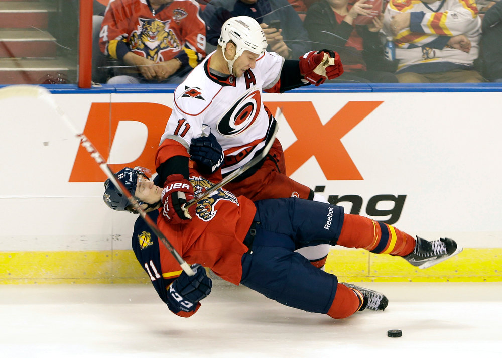 Description of . Florida Panthers center Jonathan Huberdeau, bottom, and Carolina Hurricanes center Jordan Staal battle for the puck during the first period of an NHL hockey game on Saturday, Jan. 19, 2013, in Sunrise, Fla. (AP Photo/Wilfredo Lee)