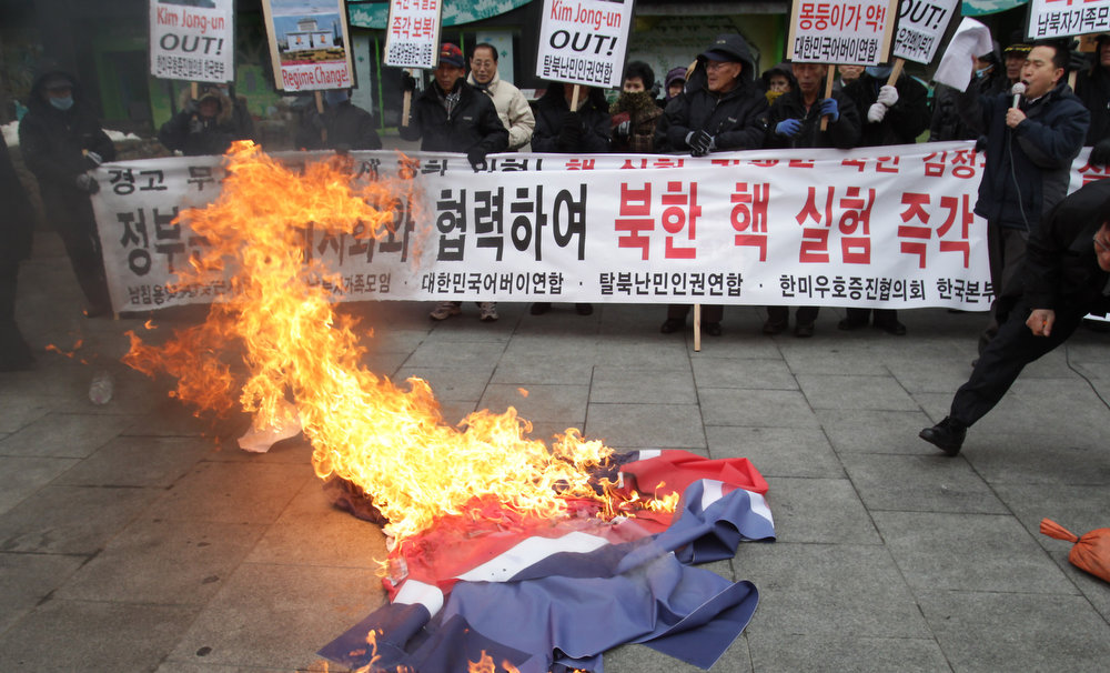Description of . SEOUL, SOUTH KOREA - FEBRUARY 12:  South Korean conservative protesters deface a North Korean flag during a rally demonstrating against North Koreas nuclear test on February 12, 2013 in Seoul, South Korea. North Korea confirmed it had successfully carried out an underground nuclear test as a shallow earthquake with a magnitude of 4.9 was detected by several international monitoring agencies. South Korea and Japan both assembled an emergency meeting of their respective national security teams after the incident.  (Photo by Chung Sung-Jun/Getty Images)