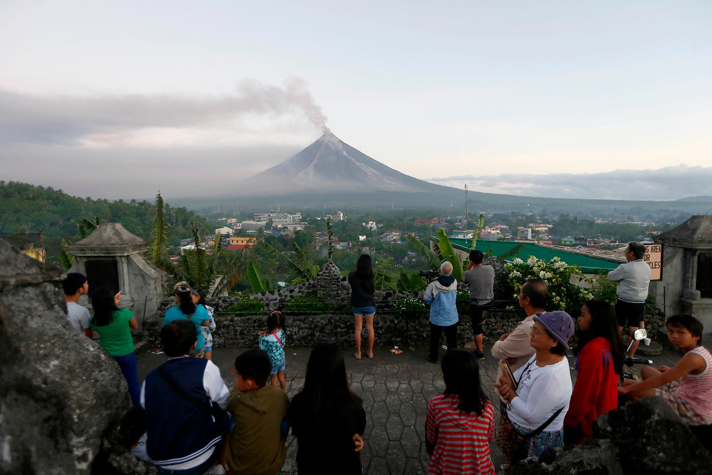 . Residents watch as Mayon volcano spews ash anew during its eruption for the second straight day Tuesday, Jan. 23, 2018 as seen from Legazpi city, Albay province, around 340 kilometers (200 miles) southeast of Manila, Philippines. The Philippines\' most active volcano ejected a huge column of lava fragments, ash and smoke in another thunderous explosion at dawn Tuesday, sending thousands of villagers back to evacuation centers and prompting a warning that a violent eruption may be imminent. (AP Photo/Bullit Marquez)