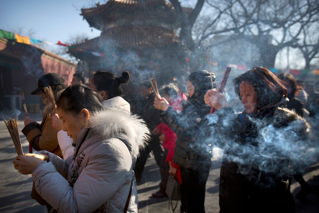 . People pray on the first day of the Lunar New Year at the Lama Temple in Beijing, Friday, Feb. 16, 2018. Chinese around the world celebrated the arrival of the Year of the Dog on Friday with family reunions, firecrackers and traditional food. (AP Photo/Mark Schiefelbein)