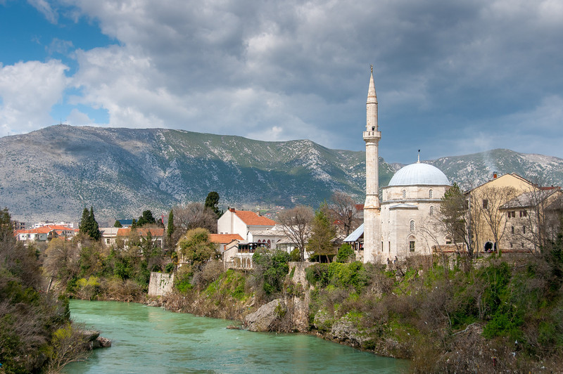 Hadzi Alija Mosque Tower and town near Neretva River in Mostar, Bosnia and Herzegovina
