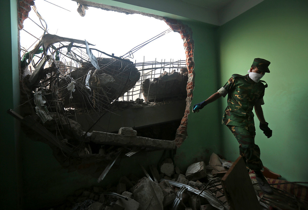 . A Bangladeshi army soldier walks in the rubble at the site of a building that collapsed Wednesday in Savar, near Dhaka, Bangladesh, Thursday, April 25, 2013. (AP Photo/Kevin Frayer)