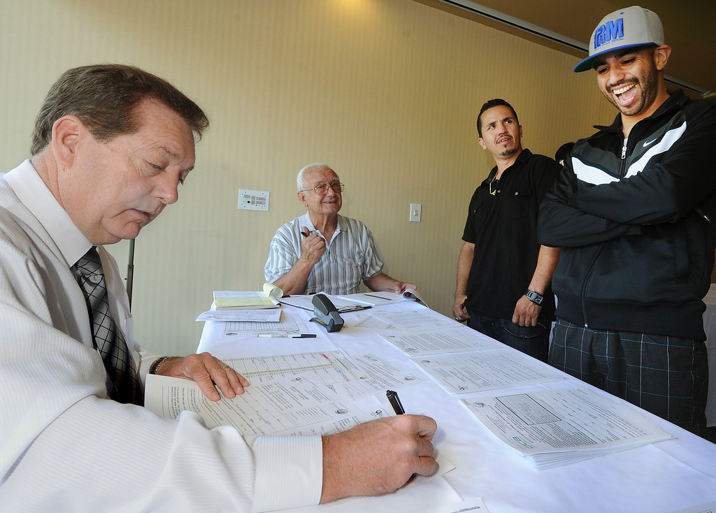 . Mark Relyea, one of the boxing commissioners checking medical and other requirements for  LAPD Officer Juan Bustamante, 30,  of Azusa in his first pro fight.  Bustamante  has been amateur boxing for 15 years, but he finally took the steps to go pro and was signed by a promotion company ahead of his debut fight on Friday, Sept. 20. The weigh-in Thursday, September 19, 2013 was held at Quiet Cannon in Montebello, where he had to lost about 20 pounds from his previous fighting weight. (Photos by Walt Mancini/Pasadena Star-News)