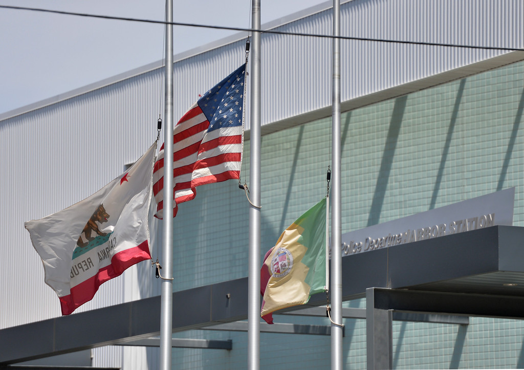 . With the flags at half mast Los Angeles police officers and firefighters lined the street in front of the Harbor Division as the coroners van was lead in procession with Officer Roberto Sanchez. San Pedro May 3, 2014. (Photo by Brittany Murray / Daily Breeze)